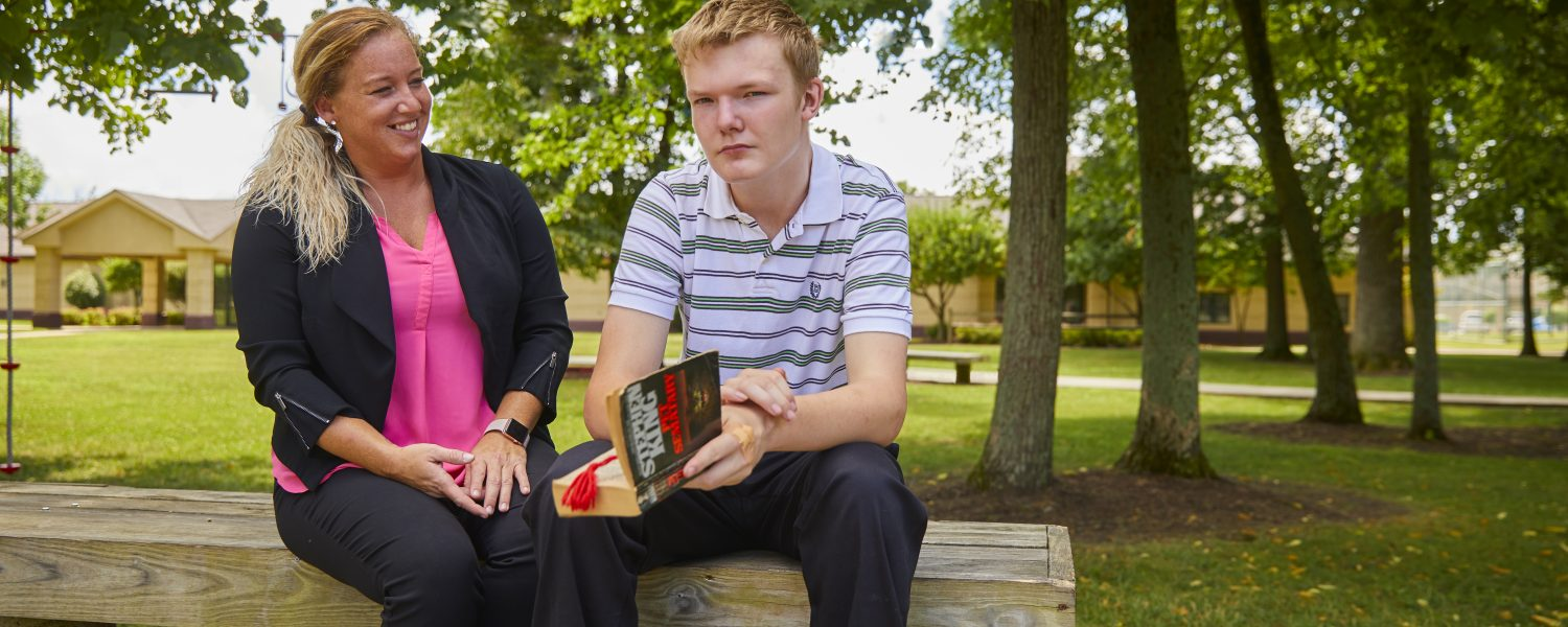 Female staff member and adolescent male client with book