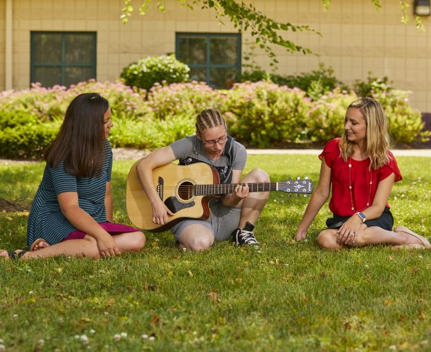 Adolescent female playing guitar for two staff members