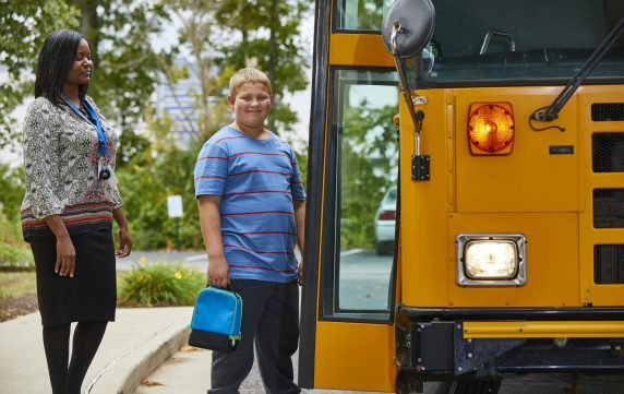 Adolescent Male Getting on School Bus