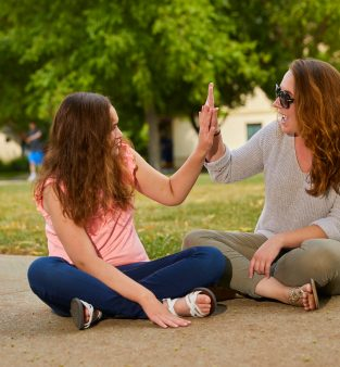 Women and female adolescent high fiving