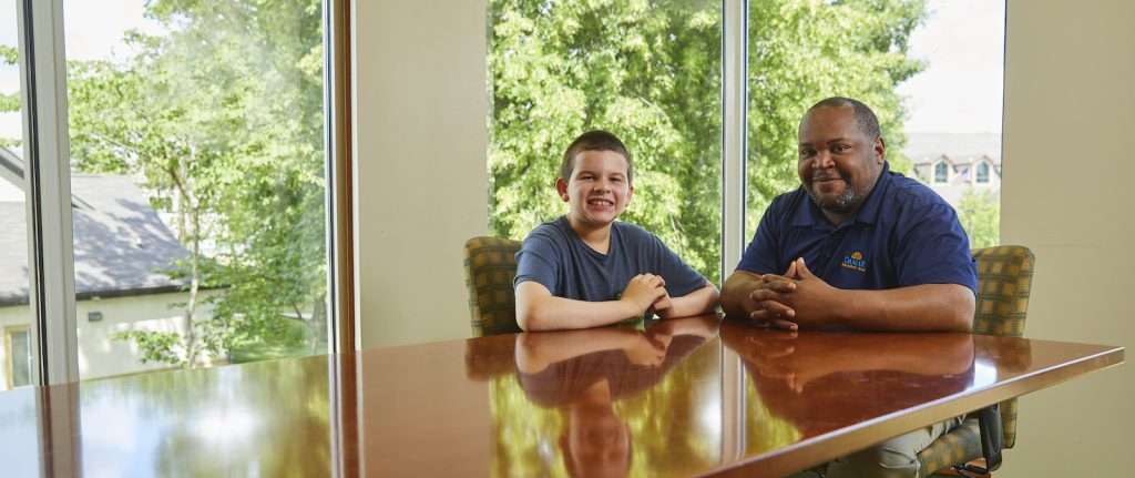 Adolescent male client and male staff member smiling
