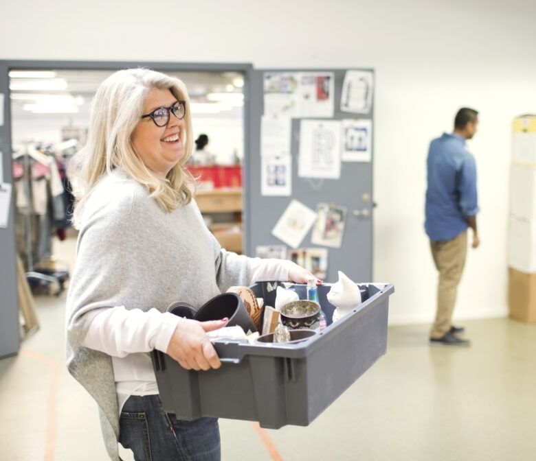 Smiling volunteer carrying crate